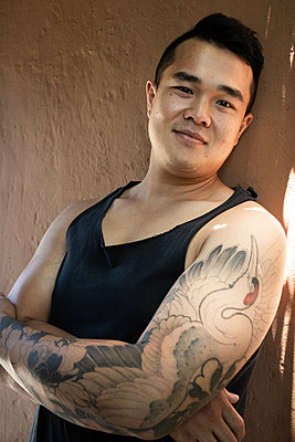 Young man with tattoo on his arm - p1640m2245811 by Holly & John