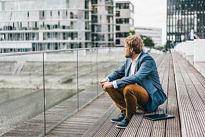 Businessman sitting on bridge having coffee break - p300m1176049 by Kniel Synnatzschke