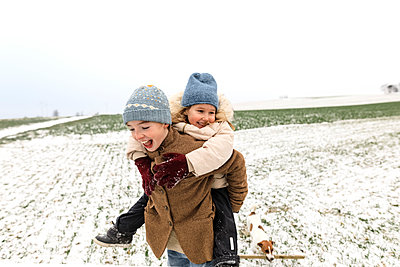 Boy carrying happy sister piggyback in winter landscape - p300m2080970 by Katharina Mikhrin