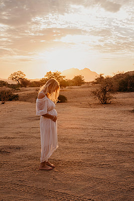 Namibia, Spitzkoppe, woman in white dress in desert landscape at sunset - p300m2081066 by letizia haessig photography