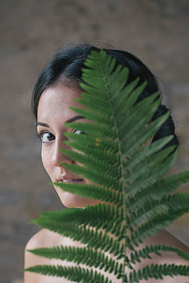Beautiful young woman hiding behind fern leaves - p300m2197300 by Alberto Bogo