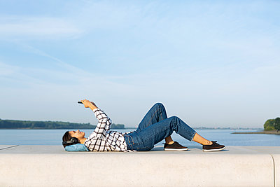 Young listenting to music at the Elbe river - p341m2210438 by Mikesch
