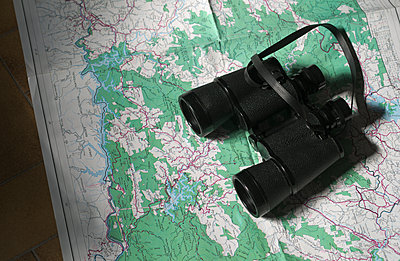 Binoculars on map - p564m2284409 by Dona