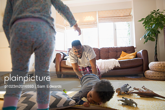 Playful father and children in living room - p1023m2016593 by Sam Edwards