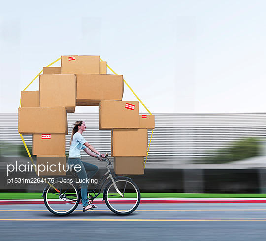 Woman Riding Bicycle Carrying Moving Boxes - p1531m2264175 by Jens Lucking
