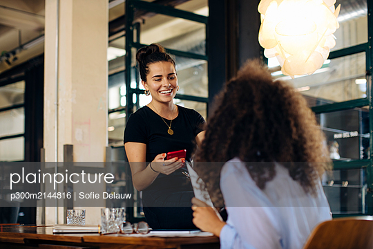 Two happy young businesswomen with smartphone in loft office - p300m2144816 by Sofie Delauw