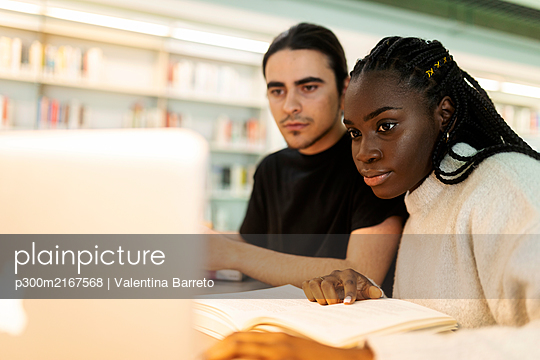 Two students with laptop and book learning in a library - p300m2167568 by Valentina Barreto