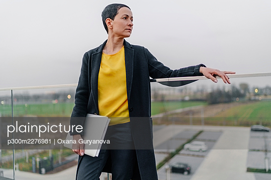 Female entrepreneur with laptop looking away while leaning on railing against sky - p300m2276981 by Oxana Guryanova