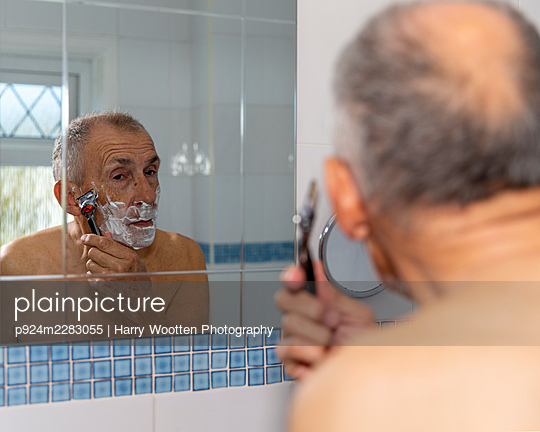 UK, East Sussex, Senior man shaving in front of bathroom mirror - p924m2283055 by Harry Wootten Photography