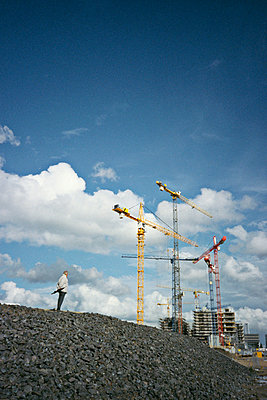 Man is looking at a construction site - p1092m880488 by Rolf Driesen