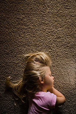 Overhead view of girl sleeping on rug at home - p1166m1182563 by Cavan Images
