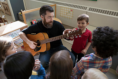 Male teacher with guitar teaching preschool students in classroom - p1192m1560126 by Hero Images
