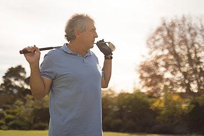 Senior man holding golf stick in golf course - p1315m1518615 by Wavebreak