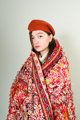 Asian woman with knit hat wrapped in a carpet - p1508m2168807 by Mona Alikhah