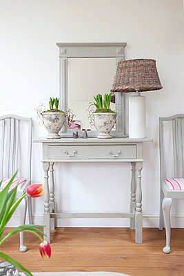 Rattan lamp on grey painted side table with mirror  Sussex home detail  UK - p3493570 by Robert Sanderson