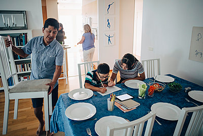 Teenage girl assisting brother in homework while father arranging chairs at dining table - p426m1517881 by Maskot