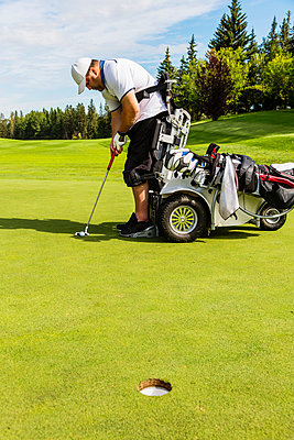 A physically disabled golfer lining up his shot before putting a ball on a golf green and using a specialized golf assistance motorized hydraulic wheelchair; Edmonton, Alberta, Canada - p442m2019734 by LJM Photo