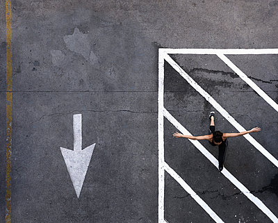 Aerial view of Pacific Islander woman doing lunges in parking lot - p555m1219406 by Colin Anderson