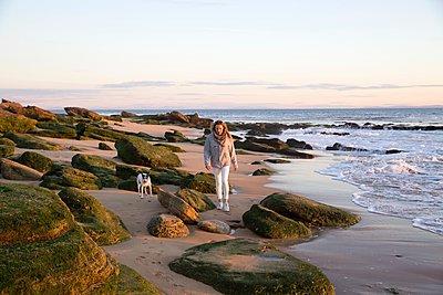 Woman walking dog on rocky beach, Cape of Trafalgar, Spain - p924m1125799f by Zak Kendal