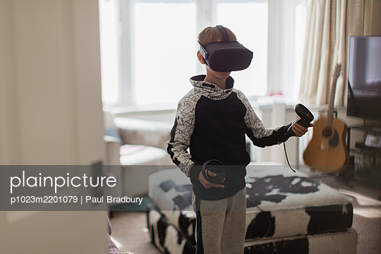 Boy playing video game with VRS goggles in living room - p1023m2201079 by Paul Bradbury