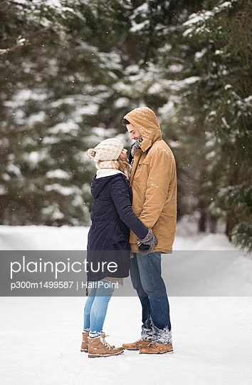 Happy young couple standing face to face in snow-covered winter landscape