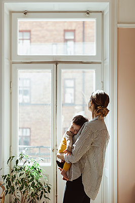 Mother carrying male toddler while looking through window at home - p426m2279816 by Maskot