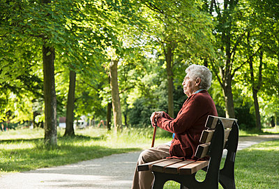 Senior woman sitting on park bench - p429m942741f by Uwe Umstaetter
