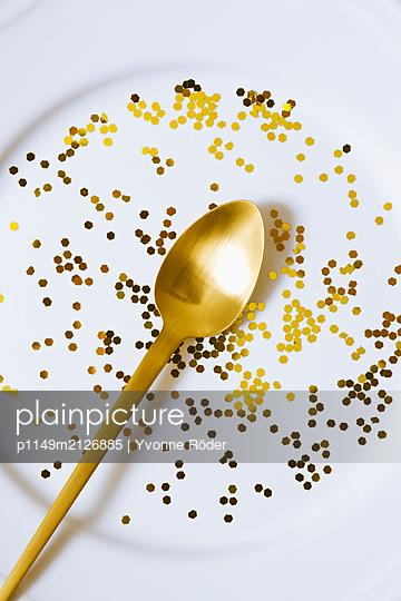 Goldener Löffel auf dekoriertem Teller - p1149m2126885 von Yvonne Röder