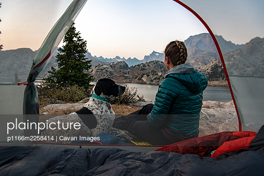 Woman sitting with dog by tent while camping during vacation - p1166m2258414 by Cavan Images