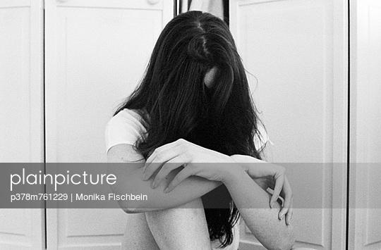 Woman sitting by wardrobe - p378m761229 by Monika Fischbein