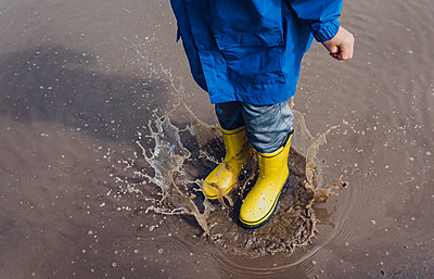 Low section of playful boy wearing yellow rubber boots while splashing puddle - p1166m2011827 by Cavan Images