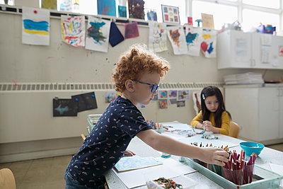 Preschool boy coloring in classroom - p1192m1560082 by Hero Images