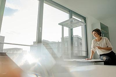 Businesswoman working in  office, sitting on desk - p300m2029817 von Kniel Synnatzschke