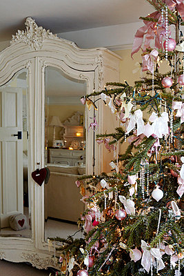 Christmas tree with pink decoration and mirrored wardrobe - p349m789728 by Brent Darby