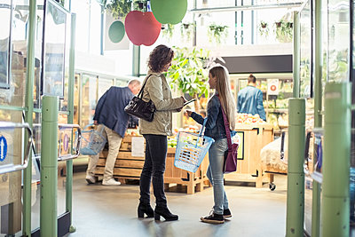 Side view of mother and daughter standing at organic supermarket - p426m1407408 by Kentaroo Tryman