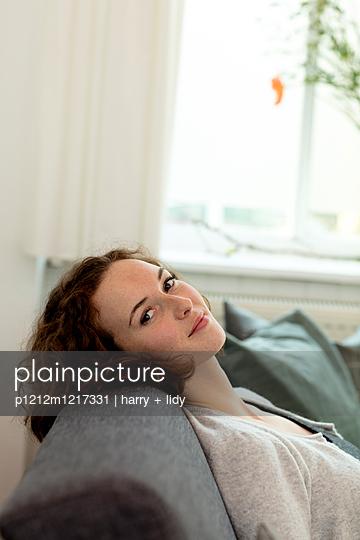 Junge Frau enstpannt sich auf dem Sofa - p1212m1217331 von harry + lidy