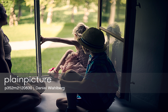 Children climbing out window - p352m2120830 by Daniel Wahlberg