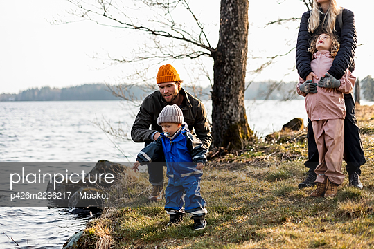 Man and woman with son and daughter by lake at park - p426m2296217 by Maskot