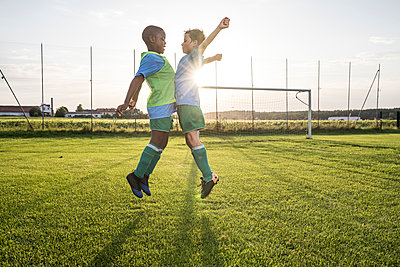 Young football players jumping on football ground - p300m1580840 by Fotoagentur WESTEND61