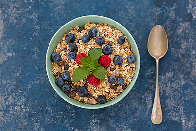 Bowl of muesli with raspberries and blueberries - p300m2029595 by JLPfeifer