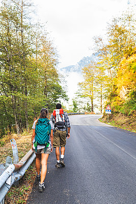 Italy, Massa, rear view of young couple walking on asphalt road in the Alpi Apuane mountains - p300m2063044 von William Perugini