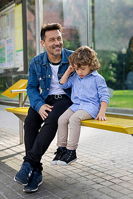 Father and son sitting at tram stop in the city sharing earbuds - p300m2070428 von Mauro Grigollo