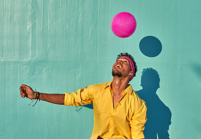 Young black man playing with a pink ball in front of a blue wall - p300m2132591 by Veam