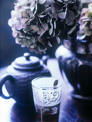 Purple hydrangea and teapot with teaspoon in glass. - p349m2167836 by Polly Wreford