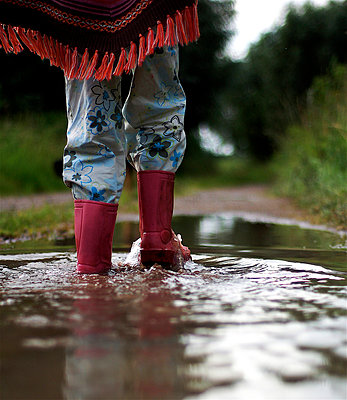 Child splashes about in puddle - p896m834700 by Richard Brocken