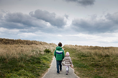 Siblings walking past field of dry grass - p924m2165195 by Bonfanti Diego