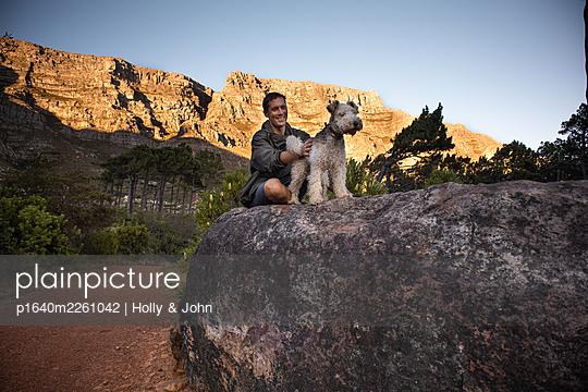 Hiker with dog on boulder - p1640m2261042 by Holly & John