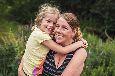 Portrait of happy mother carrying daughter while standing on grassy field in forest - p1166m2067212 by Cavan Images