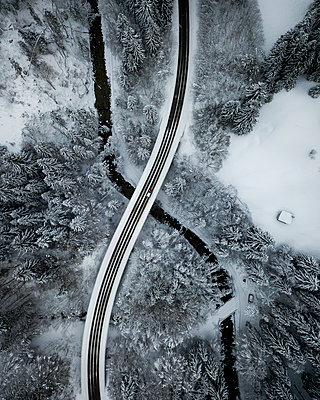 Aerial view of asphalt road stretching over river Ach flowing through snow-covered forest - p300m2206844 by Matthias Aletsee