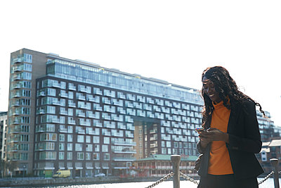 Smiling female professional using smart phone in city against clear sky - p300m2241593 by Pete Muller
